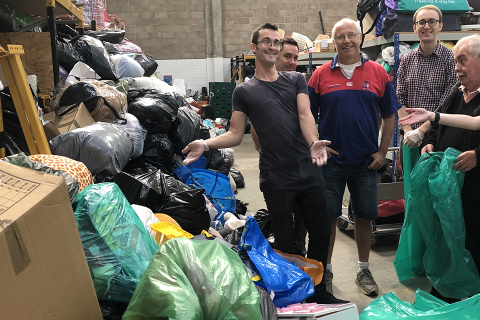 People standing next to bags of toys in a large warehouse