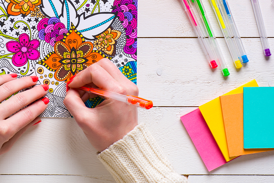 Woman colouring in a mindfulness colouring book with a pen
