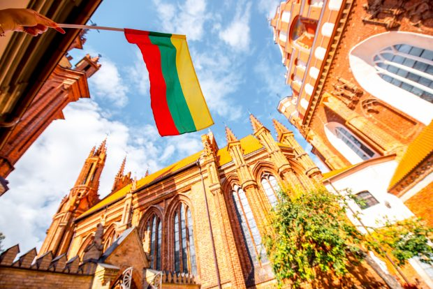 Saint Anna and Francis of Assisi churches with hand holding a Lithuanian flag in the old town of Vilnius city, Lithuania.
