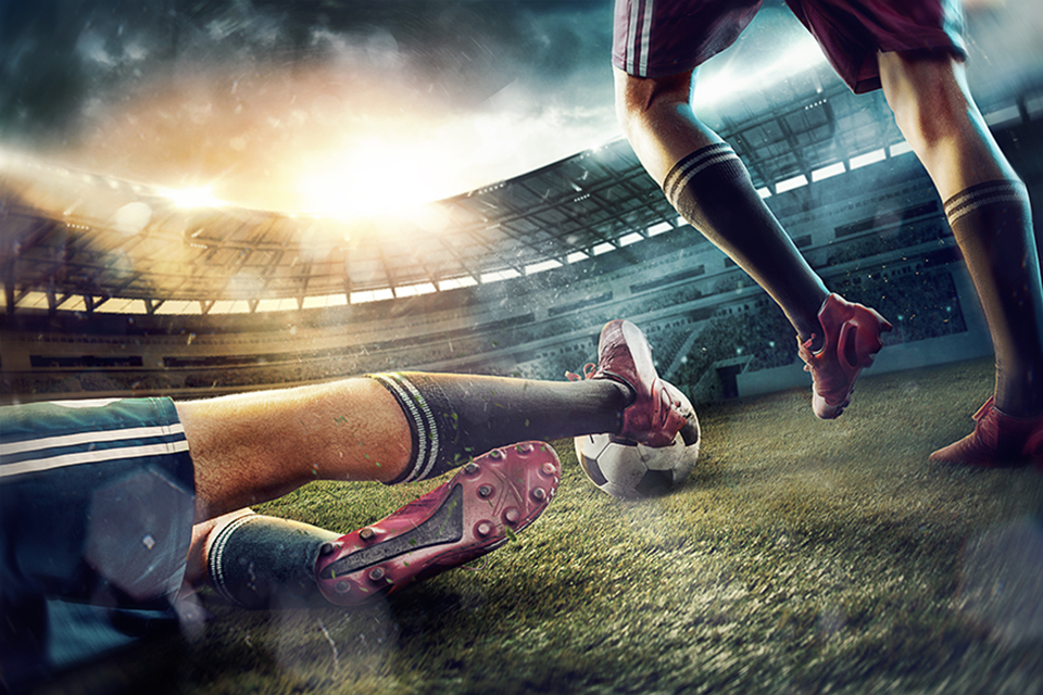 The legs of football players on green field of the stadium.